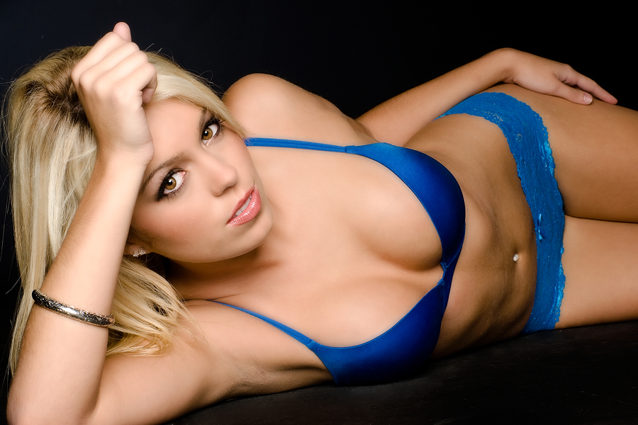 Blonde model posing in lingerie in a studio environment